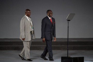 """Zimbabwe's President Robert Mugabe (R) walks to the podium to address the India-Africa Forum Summit in New Delhi on October 29, 2015. India's Prime Minister Narendra Modi has called for a """"comprehensive and concrete"""" agreement on climate change in December, as he addressed African leaders at a major summit in New Delhi.  Modi said no one had contributed less to global warming than India and Africa, warning that """"the excess of (the) few cannot become the burden of many"""".   AFP PHOTO /ROBERTO SCHMIDT"""